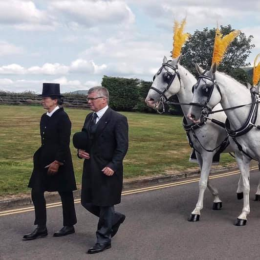funeral service employees leading two horses